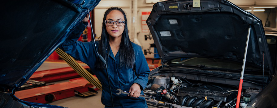 A woman in a mechanic's uniform stands next to a car with the hood open.