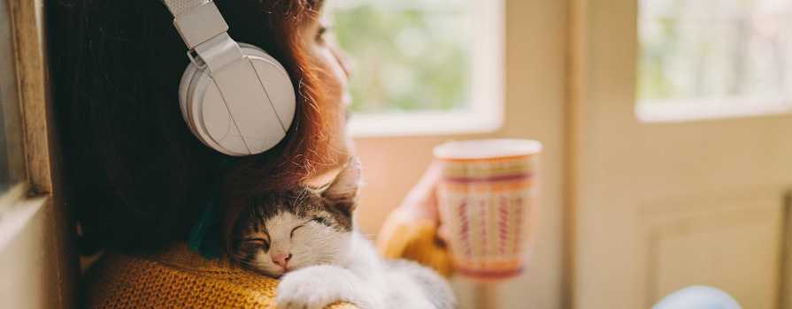 A woman sitting down with headphones on and drinking a cup of tea while holding her cat.