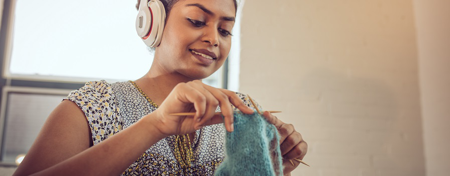A woman listening to music with headphones on while knitting.